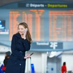 57103781 - young woman in international airport near the flight information board, using her mobile phone
